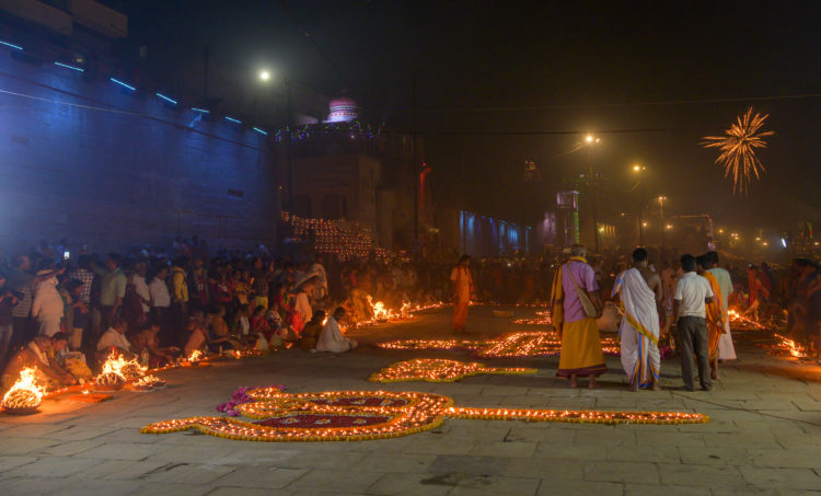 people lighting oil lamps in Ganges riverfront