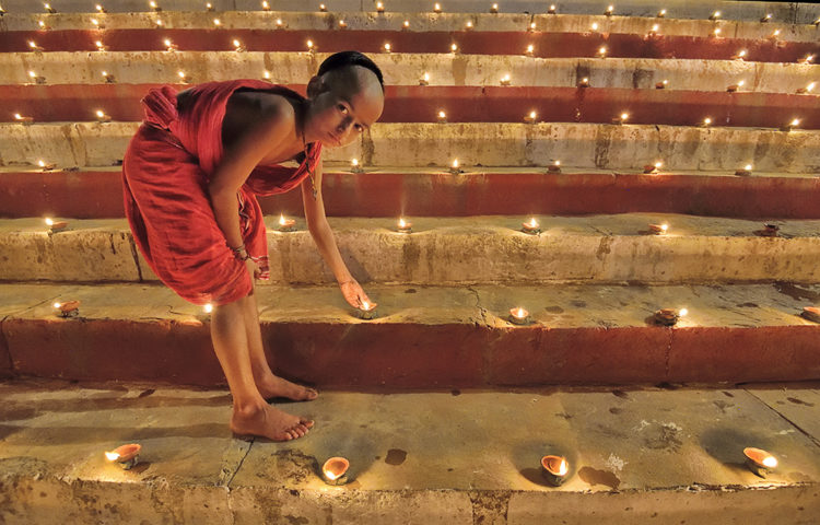 a little monk lighting lamps on Ganges riverfront
